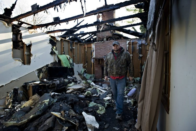 Larry Sorrell walks through the living room of his rental home that was destroyed by fire early Sunday morning.   Rich Cooley/Daily